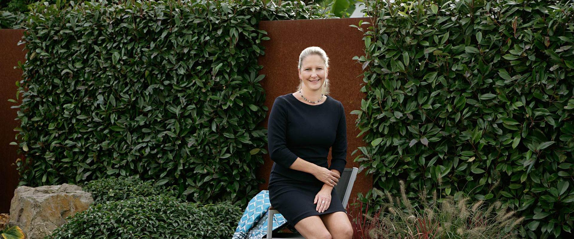 Die Geschäftsführerin von positiv abheben sitzt lächelnd vor einer grünen Hecke was ihren Wert Natur widerspiegelt